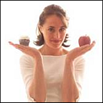 Woman holding an apple and a cupcake.